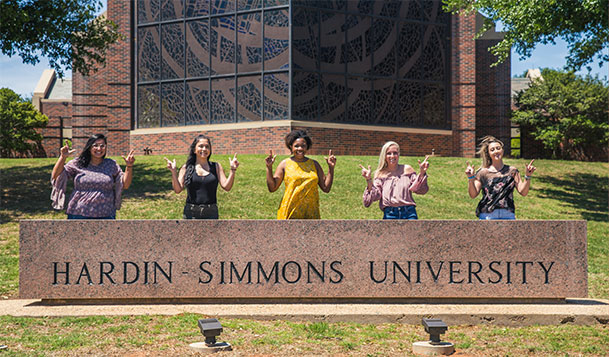 Group of female students standing behind university sign